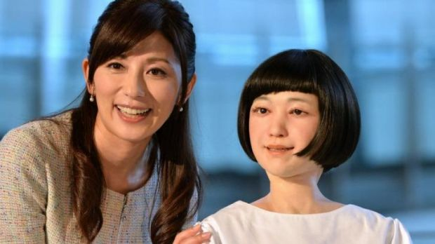"Japanese announcer Aki Nakata (left) smiles as she poses with a new humanoid robot named ""Kodomoroid"" at the National ..."