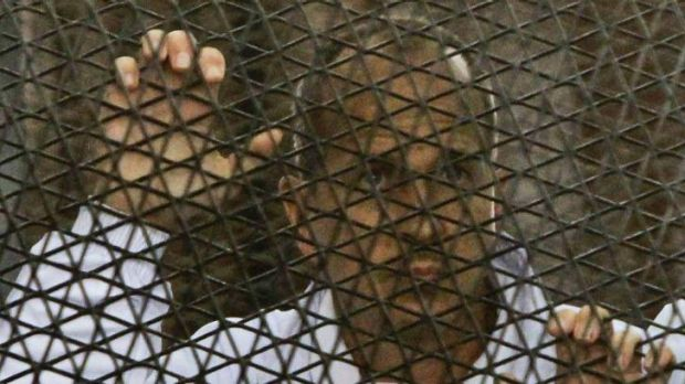 Al Jazeera journalist and Australian citizen Peter Greste stands inside the defendants' cage in a courtroom during the trial.