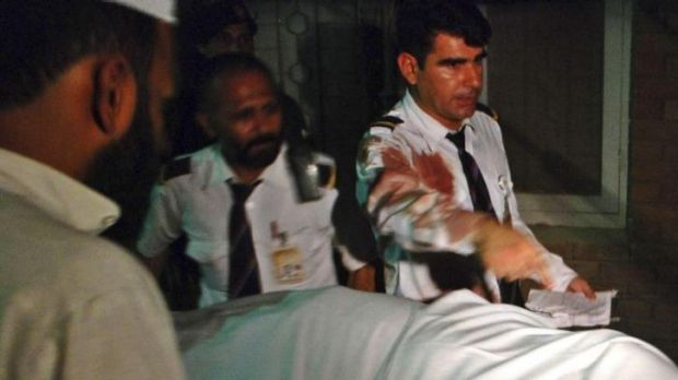 Plane attack: Crew members of a Pakistan International Airlines plane are seen beside the body of a woman who was killed ...