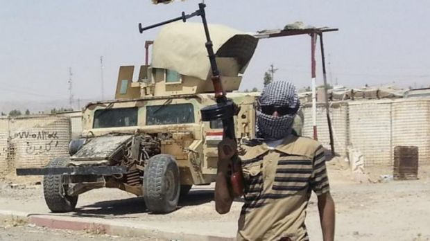 A fighter of the Islamic State of Iraq and the Levant (ISIL) stands guard at a checkpoint near Baiji, north of Baghdad.