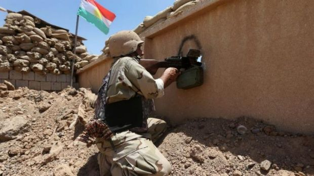 A Kurdish peshmerga fighter takes his position behind a wall on the front line with militants from the Islamic State in ...