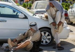 Preparing for battle. Members of an Iraqi volunteer force put on their newly issued boots in the Shiite holy city of ...