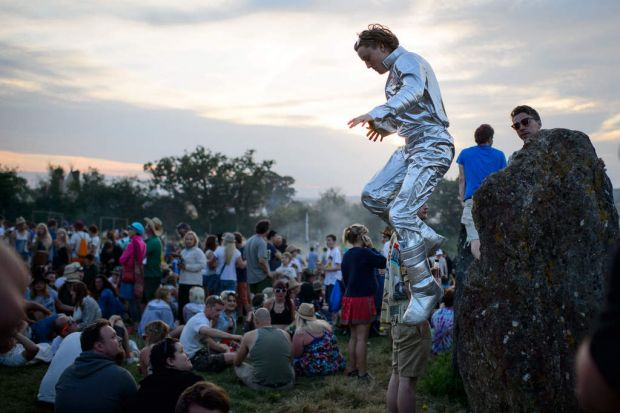 A man in a spacesuit jumps from one of the standing stones in the stone circle, as revelers gather ahead of this ...