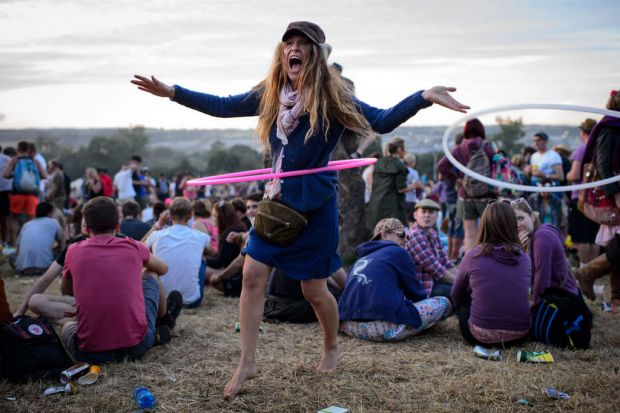 A festival goer uses a hula hoop, as revelers gather ahead of this weekends Glastonbury Festival.