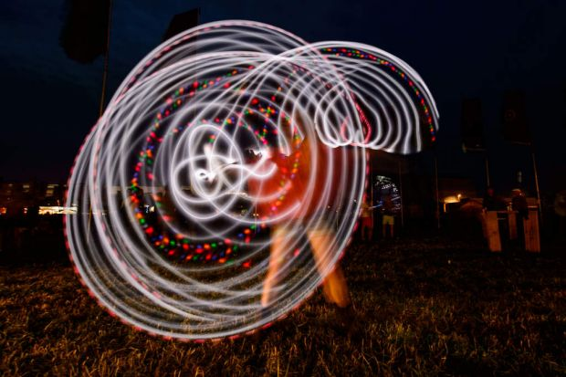A girl uses a glowing hula hoop, as revellers gather ahead of this weekends Glastonbury Festival.