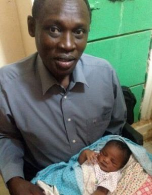 Daniel Wani carrying his newborn daughter Maya at the women's prison before Meriam Ibrahim's release.