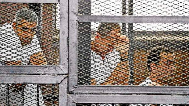 Al-Jazeera's Mohammed Fahmy, Peter Greste and Baher Mohamed appear in a defendant's cage during their trial in May.