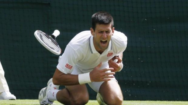 Novak Djokovic of Serbia shouts in pain after falling.