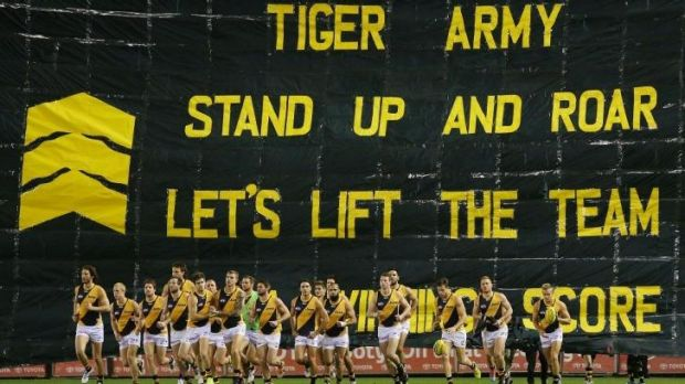 The Tigers run through the banner before the start of the game.