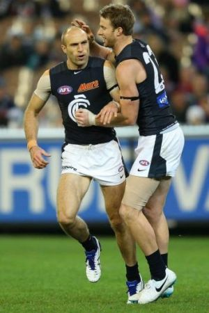Chris Judd celebrates a goal with Lachie Henderson on Sunday.