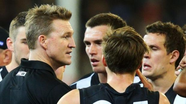 Nathan Buckley and his players talk strategy during a break in the game.