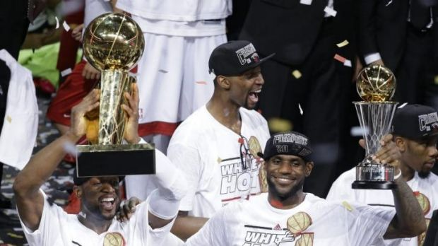 the Miami Heat's Dwyane Wade, left, holds Dwayne Wade with the NBA Championship Trophy in 2013.