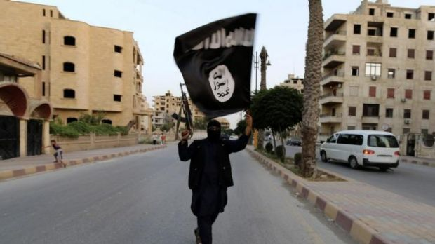 "Islamic State of Iraq and the Levant loyalist waves an ISIL flag after the ''caliphate"" was declared."