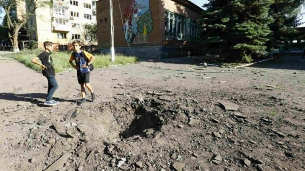Boys stand near a shell crater outside a local school in the eastern Ukrainian town of Kramatorsk.