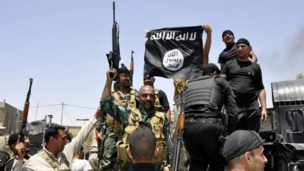 Fighting back ... Iraqi security forces pull down a flag belonging to Sunni militant group Islamic State of Iraq and the ...