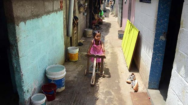 Long wait: A Tamil refugee plays between rows of houses in a Sri Lankan refugee camp at Thuraimangalam in Perambalur ...