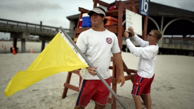 Tybee Island Ocean Rescue Senior Lifeguard Todd Horne, right, and Mark Eichenlaub, left, prepare to hang a yellow flag ...