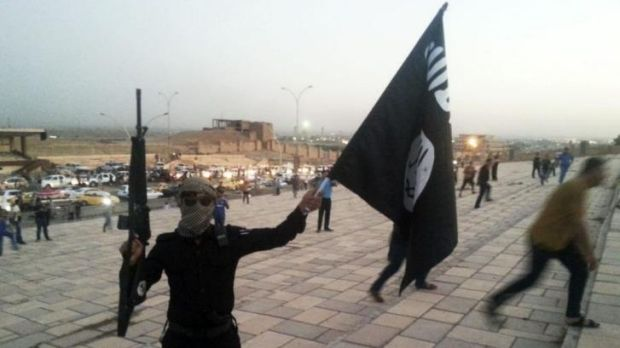An ISIL militant holds an ISIL flag and weapon in the Iraqi city of Mosul on June 23, 2014.