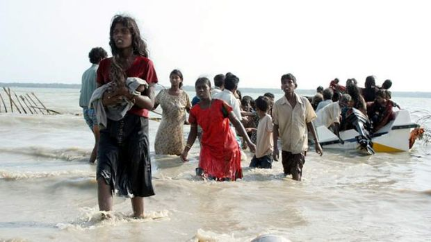 Fears asylum seekers could face torture: Photograph from May 15, 2009 shows Tamil civilians wading and using boats to ...