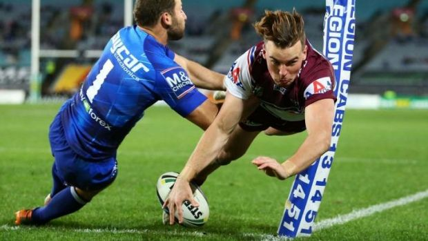 Eagle on the wing: Manly rookie Clint Gutherson dives over in the corner, around Bulldogs fullback Mitch Brown.