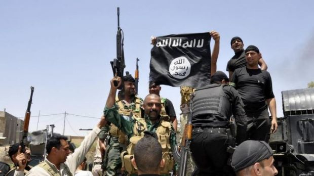 Iraqi security forces pull down a flag belonging to Sunni militant group Islamic State of Iraq and the Levant (ISIL) ...