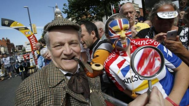 A man dressed as Sherlock Holmes poses with cycling fans prior to the start of the first stage of the Tour de France.