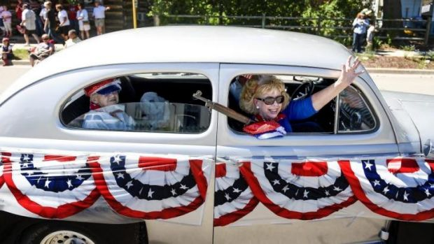 Gun rights: Joanne Canda, right, waves to parade goers during a demonstration for the Independence Day parade in ...