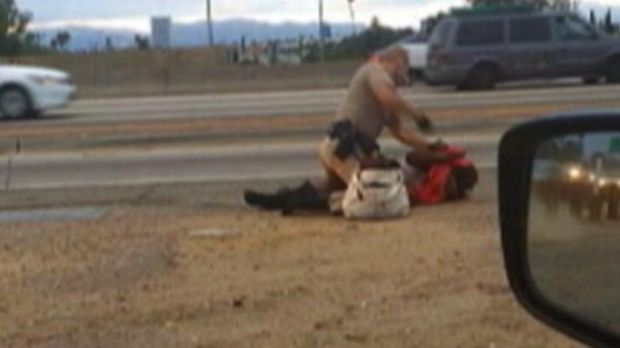A still from a passing motorist's video shows the confrontation between a California Highway Patrol officer and a woman ...