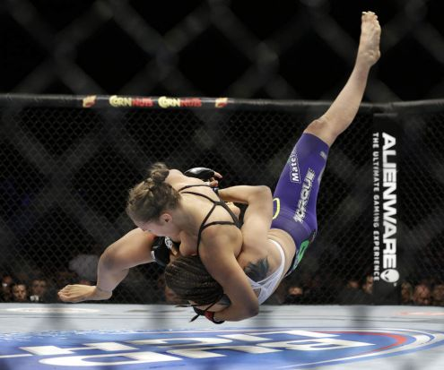 Ronda Rousey, left, takes down Alexis Davis during their women's mixed martial arts bantamweight title bout at UFC 175, ...