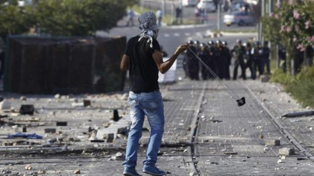A Palestinian throws stones towards Israeli police.