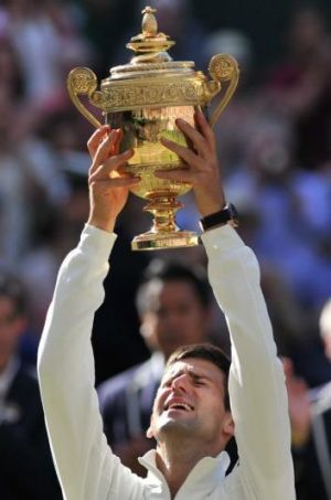 An emotional Novak Djokovic lifts the Wimbledon men's trophy on Sunday.