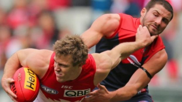 Plays in the Swans' physical style: Luke Parker fends off Melbourne's Colin Garland.