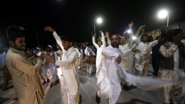 Supporters of Ashraf Ghani dance in the street after the announcement of preliminary results.