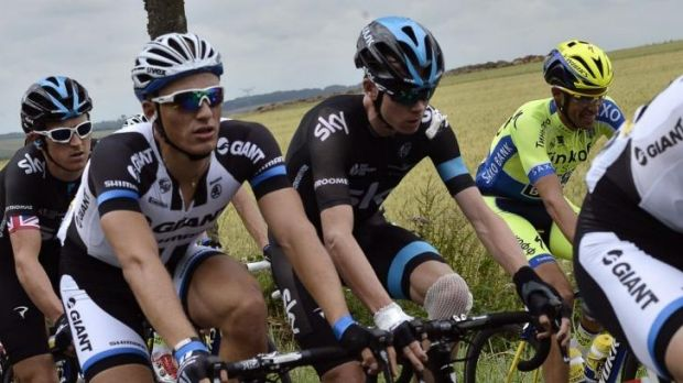 Patched up: Chris Froome, with a bandaged knee, rides near the back of the field after his fall.