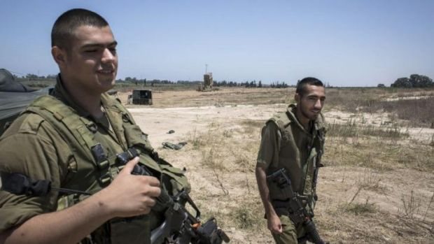 Israeli soldiers patrol near an Iron Dome air defence system in Ashkelon, Israel.