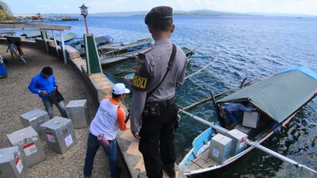 Many islands to reach ... An Indonesian policeman stands guard while officials load ballot boxes in Bau-bau, Southeast ...
