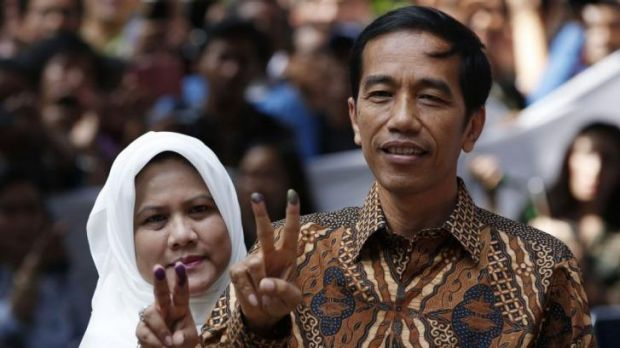 "Indonesian presidential candidate Joko ""Jokowi"" Widodo and his wife Iriana after casting their vote in Jakarta on Wednesday."