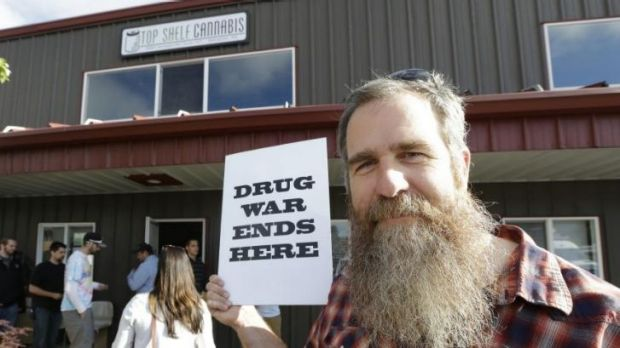 Kevin Nelson holds a sign outside Top Shelf Cannabis in Bellingham, Washington.