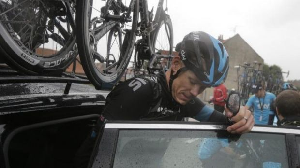 Chris Froome gets into his team's car after crashing.