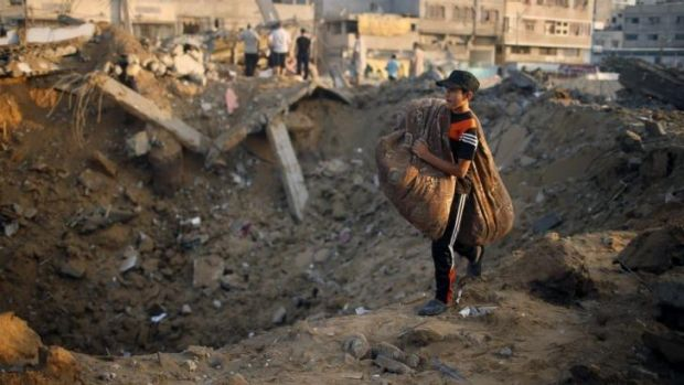 A Palestinian boy carries his belongings past what Gaza police said was the site of his family's Gaza City house ...