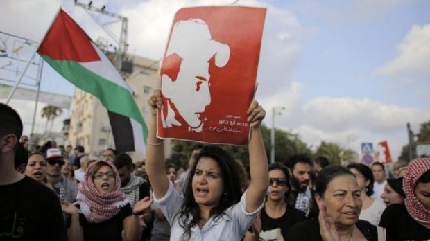 Palestinian citizens of Israel protest over the death of Mohammed Abu Khedair (pictured in poster) in the northern ...