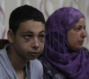 Tariq Abu Khedair sits with his slain cousin Mohammed Abu Khedair's mother before a meeting with Palestinian Authority ...