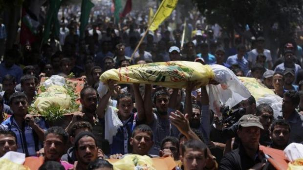Palestinians carry the bodies of seven people killed in an Israeli air strike during their funeral in the Khan Younis ...