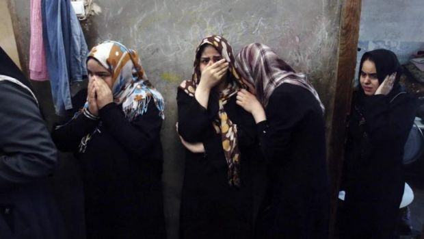 Relatives mourn the deaths of family members, killed in Israeli air strikes.