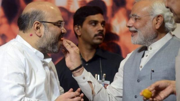 Indian Prime Minister Narendra Modi (right) gives sweets to newly appointed BJP president Amit Shah on Wednesday.