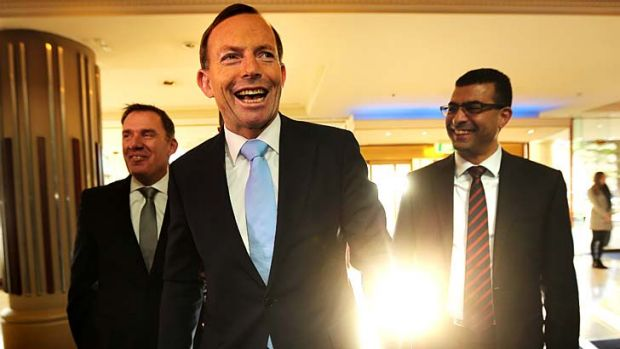 Prime Ministerial smile: Tony Abbott puts a brave face on things on Friday.