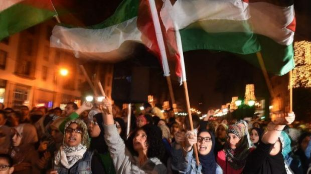 Moroccans hold placards and flags as they shout slogans during a demonstration in supporting Palestine.