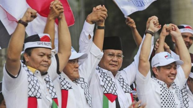Indonesian presidential candidate Prabowo Subianto, second from right, holds hands with top members of his coalition ...