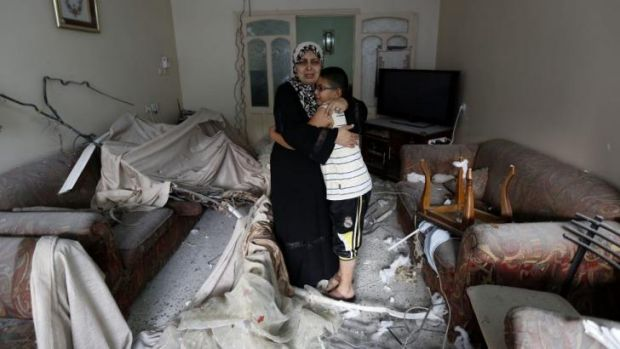 A Palestinian woman hugs her son at their damaged living room after a neighboring building was targeted in an Israeli ...