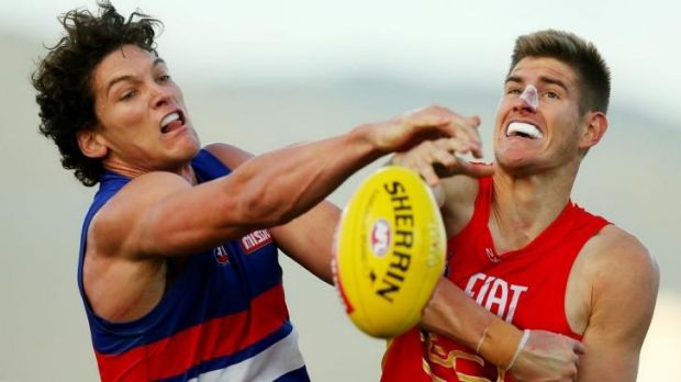 Will Minson of the Bulldogs and Zac Smith of the Suns vie for possession.